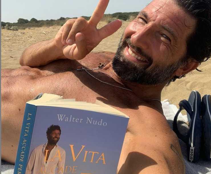 Walter Nudo in spiaggia con il suo nuovo libro (Instagram)